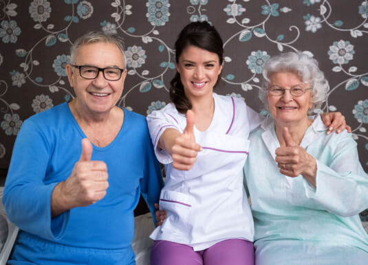 elderly couple and caregiver showing their thumbs up