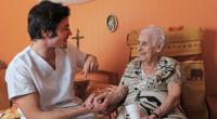 caregiver helping his patient senior