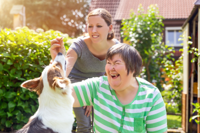 nurse and patient playing with dog