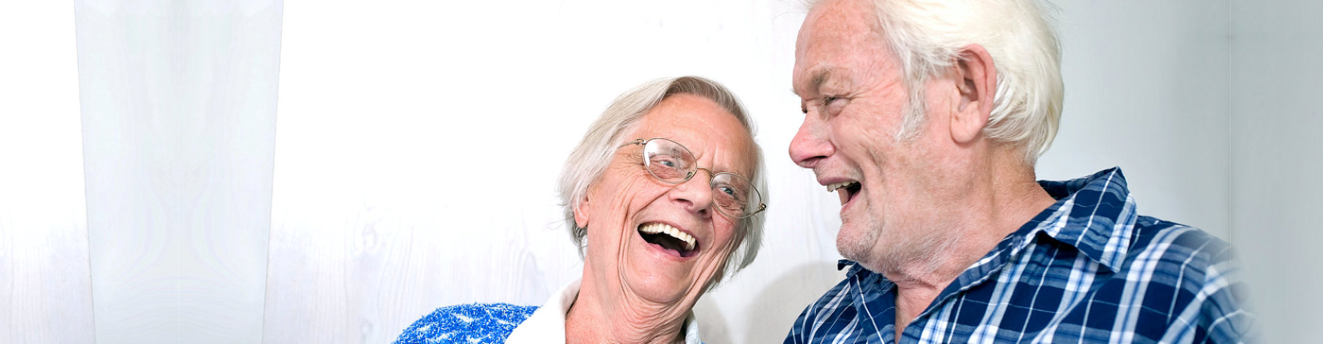 Elderly couple looking at each other laughing.