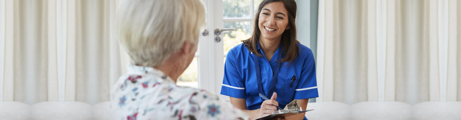 Senior woman sitting at home with care nurse taking notes